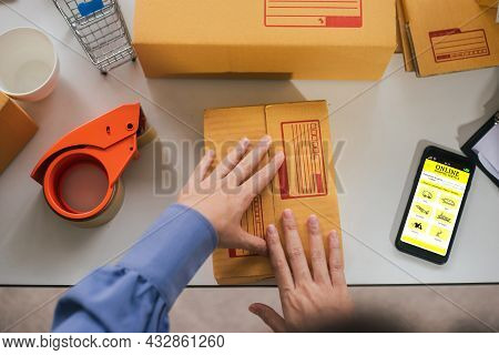 Top View Of Worker Or Seller Packing Cardboard Ecommerce Shipping Order Box For Dispatching. Prepari