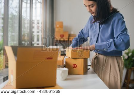 Asian Woman Worker Or Seller Packing Cardboard Ecommerce Shipping Order Box For Dispatching. Prepari