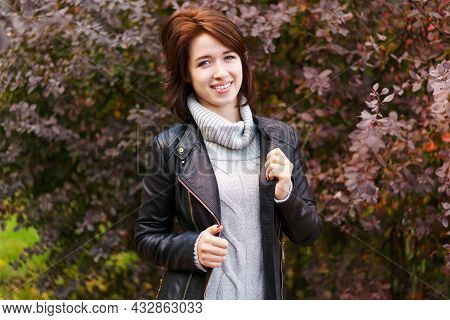 Joyful Pretty Young Happy Woman With A Beautiful Smile In A Leather Jacket And Sweater Posing In The