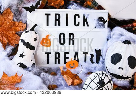Lightbox With Text Trick Or Treat Halloween Background With Painted Face Pumpkins And Autumn Leaves.