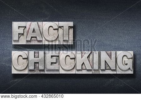 Fact Checking Phrase Made From Metallic Letterpress On Dark Jeans Background
