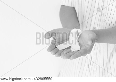 Hands Holding White Pearl Ribbon Bow On White Background, Copy Space. Lung Cancer Awareness, Mesothe