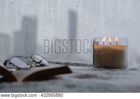 Burning Aroma Candle Puts Near By Window That Have Rain Drop In Monsoon Season With Blurred City Bac