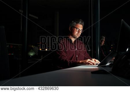 Concentrated Businessman Sitting In Dark Office Near The French Windows Using Laptop At The Late Nig