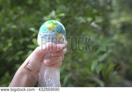 Woman Holding A Globe Of Planet Earth Wrapped With Plastic Bubble Bag. Green Nature Background.