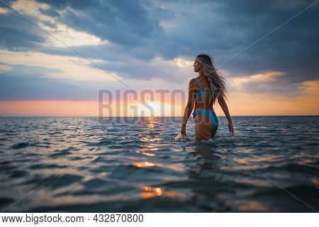 Girl With Blond Hair In A Swimsuit Posing Against The Backdrop Of The Sunset In The Estuary Enjoying