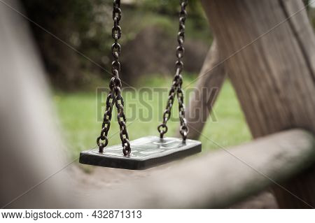 Swing Hanging Still At The Empty Playground | Close Up Photo Of A Hanging Still Swing At The Empty P