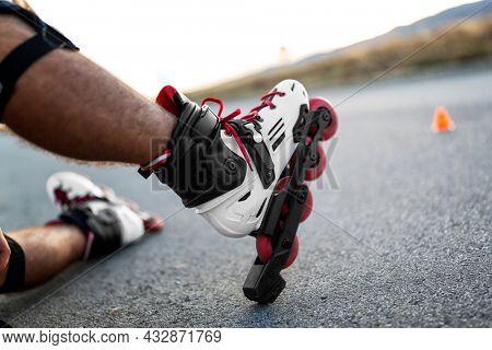 Roller skates. Inline skating on asphalt road in nature
