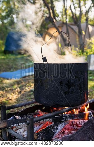 Steaming camping pot on burning campfire with cooking meal. Tents a seen in background