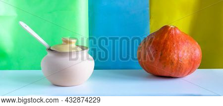 An Orange Pumpkin And A Clay Pot With A Wooden Spoon On A White Wooden Table. Autumn Background For