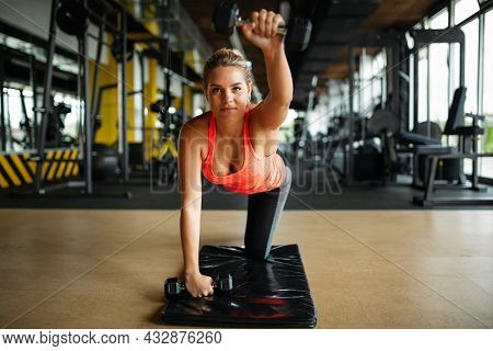 Young Muscular Fit Woman Doing Exercise On Fitness Mat In Health Club. Sport Health Fitness Concept