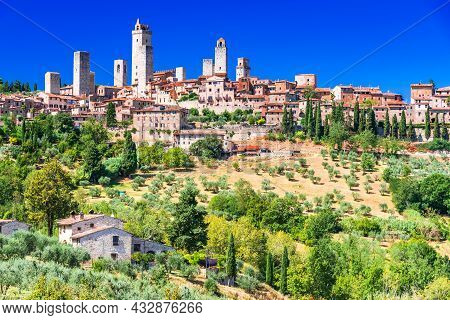 San Gimignano Medieval Town Skyline And Famous Towers Sunny Day. Italian Olive Trees In Foreground.