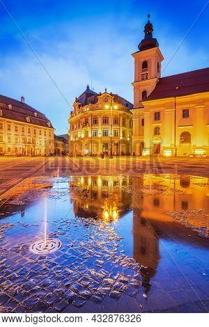 Sibiu, Romania. Twilight Scene With Water Reflection In Large Square, Transylvania Travel Sight.