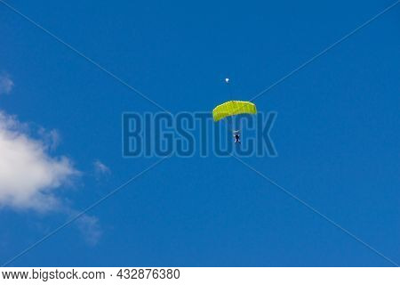 Tandem Jump Of An Amateur With A Trainer Under A Canopy Of A Green Parachute-wing