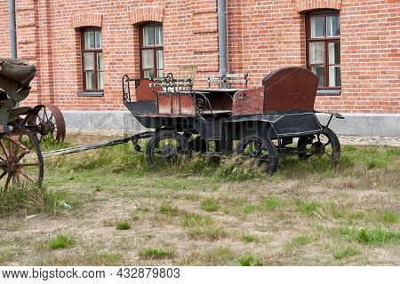 Old Carriage In A Rural Courtyard On A Summer Day