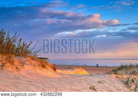 Sand Dune Illuminated By The Setting Sun And The Shore Of The Baltic Sea.