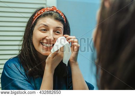 Young Happy Woman Makes A Facial Treatment Smiling In The Mirror - Concept Of Wellbeing With Oneself