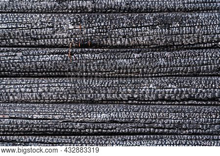 Burnt Wall Of A Wooden House Made Of Logs. The Surface Is Covered With A Black Charred Layer. Backgr