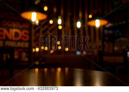Blurred Night Cafe Background. Table And Reflection On Foreground. Copy Space.