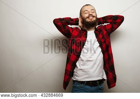 Lifestyle and people concept. A young bearded man in a red plaid shirt threw his hands behind his head.
