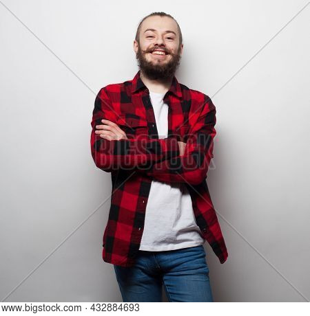 Bearded young smiling man wearing casual plaid shirt and jeans with his arms crossed over grey background
