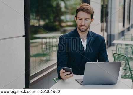Serious Male Boss Dressed In Elegant Clothes Works Online On Laptop Computer Types Text Messages Via