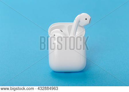 Modern Wireless Bluetooth Headphones With Charging Case On A Blue Background. The Concept Of Modern