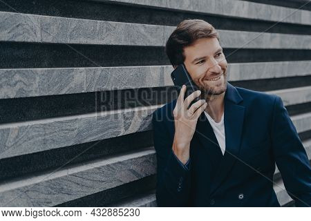 Attractive Young Office Worker In Stylish Blazer Speaking On Mobile Phone During Work Break, Smiling