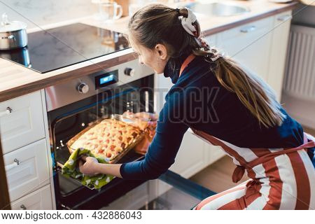 Woman baking apple pie at home