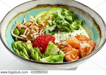 Healthy food - poke bowl with salmon, rice, cucumber, avocado, edamame beans, soybean sprouts and ponzu sauce. Hawaiian meal poke bowl with salmon isolated on white background