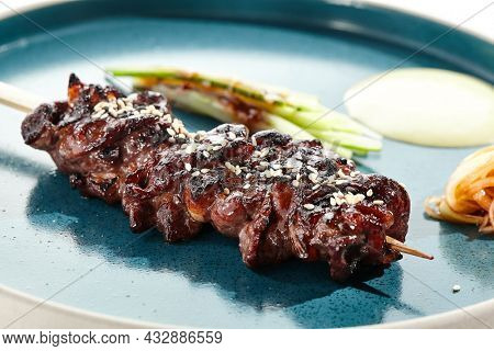 Food in Japanese restaurant - skewer yakitori with beef and teriyaki sauce. Grilled beef black Angus  on bamboo stick in Japanese style. Bbq menu for asian restaurant. Yakitori on white background