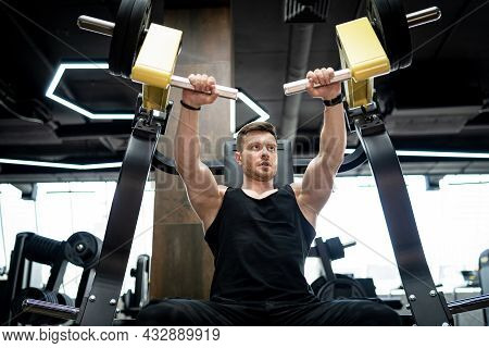 Handsome Strong Bodybuilder Doing Exercise. Muscular Athletic Man Training Hard In Gym.