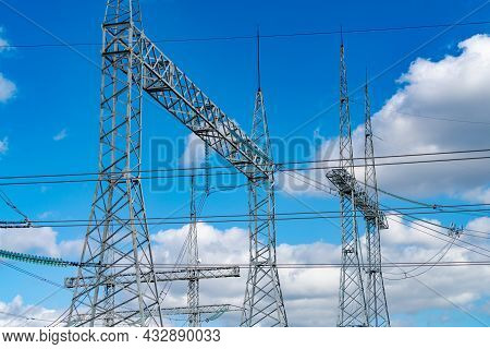 Pylons Or Transmission Towers In Countryside On Beautiful Blue Sky Background. Landscape With High-v