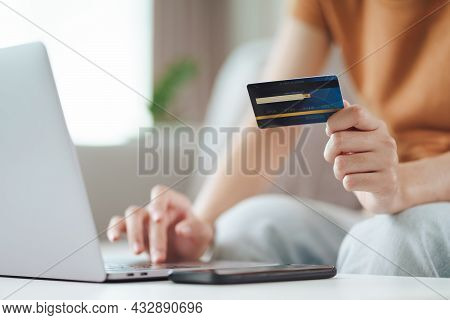 Young Woman Holding Credit Card And Using Laptop Computer. Online Shopping, Internet Banking, E-comm
