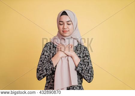 Muslim Woman Wearing Hijab Holding Chest And Eyes Closed With Patient Expression