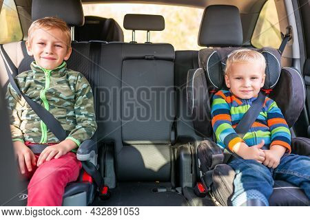 Two Little Boys Sitting On A Car Seat And A Booster Seat Buckled Up In The Car.