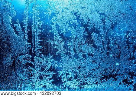 Beautiful blue frost patterns on frozen window as a symbol of Christmas wonder. Christmas or New year background.