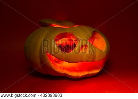 A Pumpkin Glows For The Halloween Holiday On A Red Background.