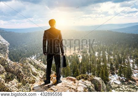 Young businessman standing and rock mountain. Mixed media