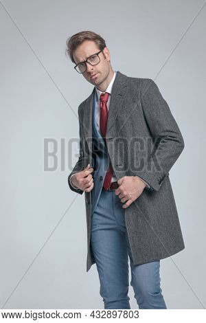 young businessman arranging his coat, wearing eyeglasses in a fashion pose