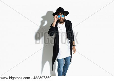 fashion model fixing his sunglasses and striking an attitude against white background