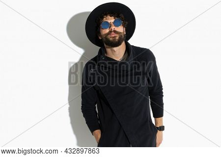 sexy casual man posing with one hand in pocket and a tough attitude against white background