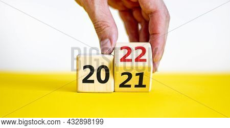 2022 Happy New Year Symbol. Businessman Turns A Cube, Symbolize The Change From 2021 To The New Year