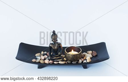 Altar With Buddha Statue, Burning Candle And Pebbles. Meditation, Buddhism And Enlightenment Concept