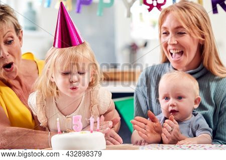 Grandmother With Mother And Grandchildren Celebrating With Fifth Birthday Party At Home