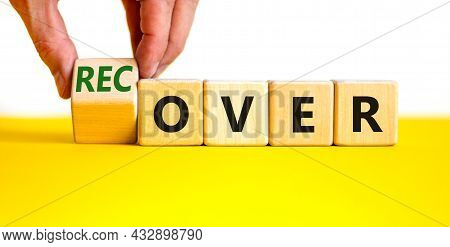 Time To Recover Symbol. Businessman Turns A Wooden Cube And Changes The Word 'over' To 'recover'. Be