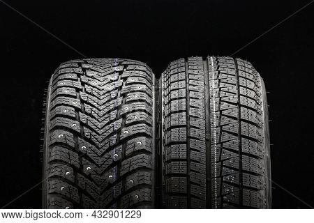 Winter Tires Wheels Are New Black Background. Friction Velcro Wheel And Studded Tire Next To Two Pie