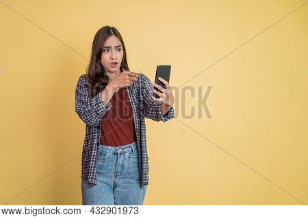 A Woman Using A Cellphone With A Surprised Gesture And Finger Pointing While Looking At A Cellphone