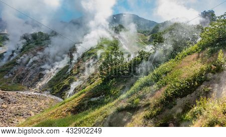 The Famous Valley Of Geysers. Kamchatka. A Small River Flows Along A Rocky Bed. Columns Of Steam Fro