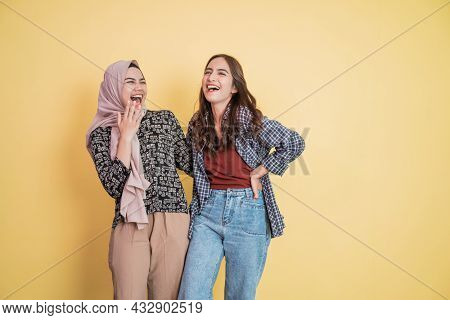Having Fun Of Two Beautiful Women Laughing While Chatting And Embracing With Hands On Shoulders With